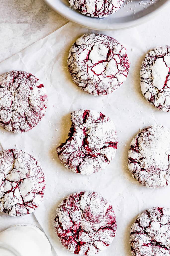 Red Velvet Crinkle Cookies Arranged on a White Placemat, Seen From Above