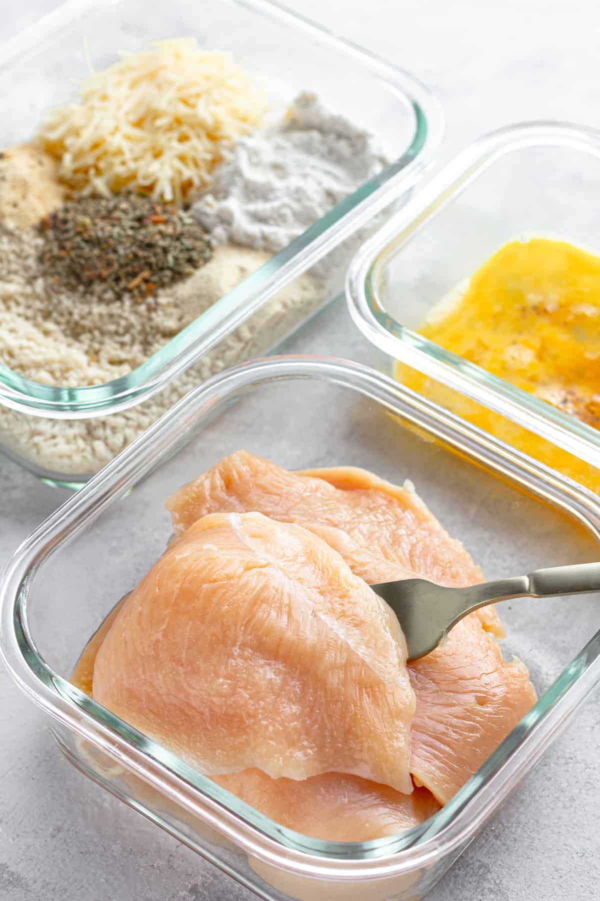 Three Glass Containers on a Counter – One Containing Raw Chicken, One Containing the Egg Mixture and One Containing the Un-Combined Breading Mixture