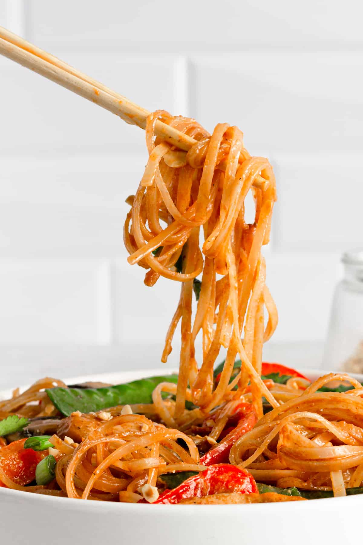 A Pair of Chopsticks Holding a Bite of Chicken Lo Mein Over the Bowl