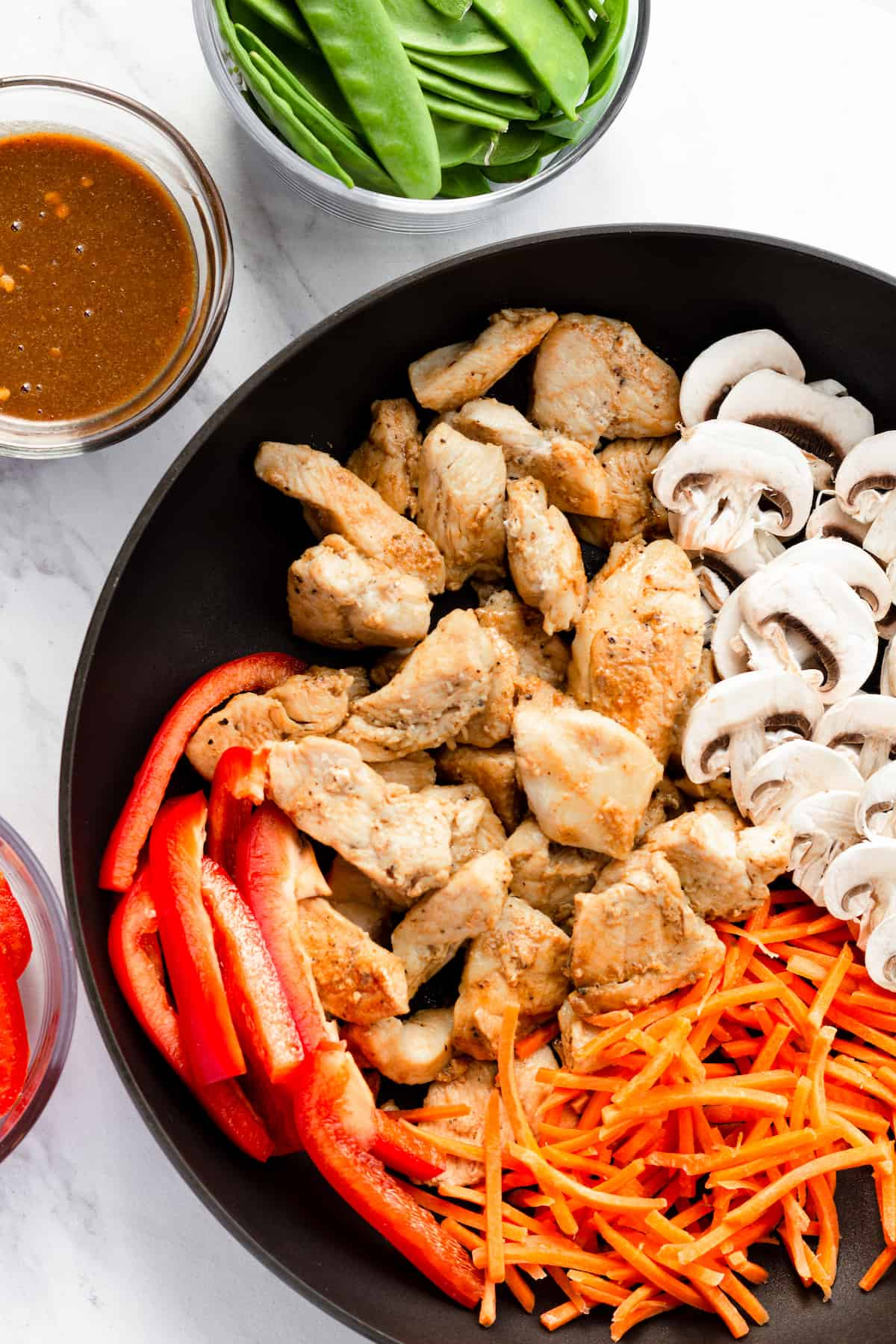Cooked Chicken, Shredded Carrots, Mushrooms and Red Pepper Slices in a Skillet Beside the Other Ingredients