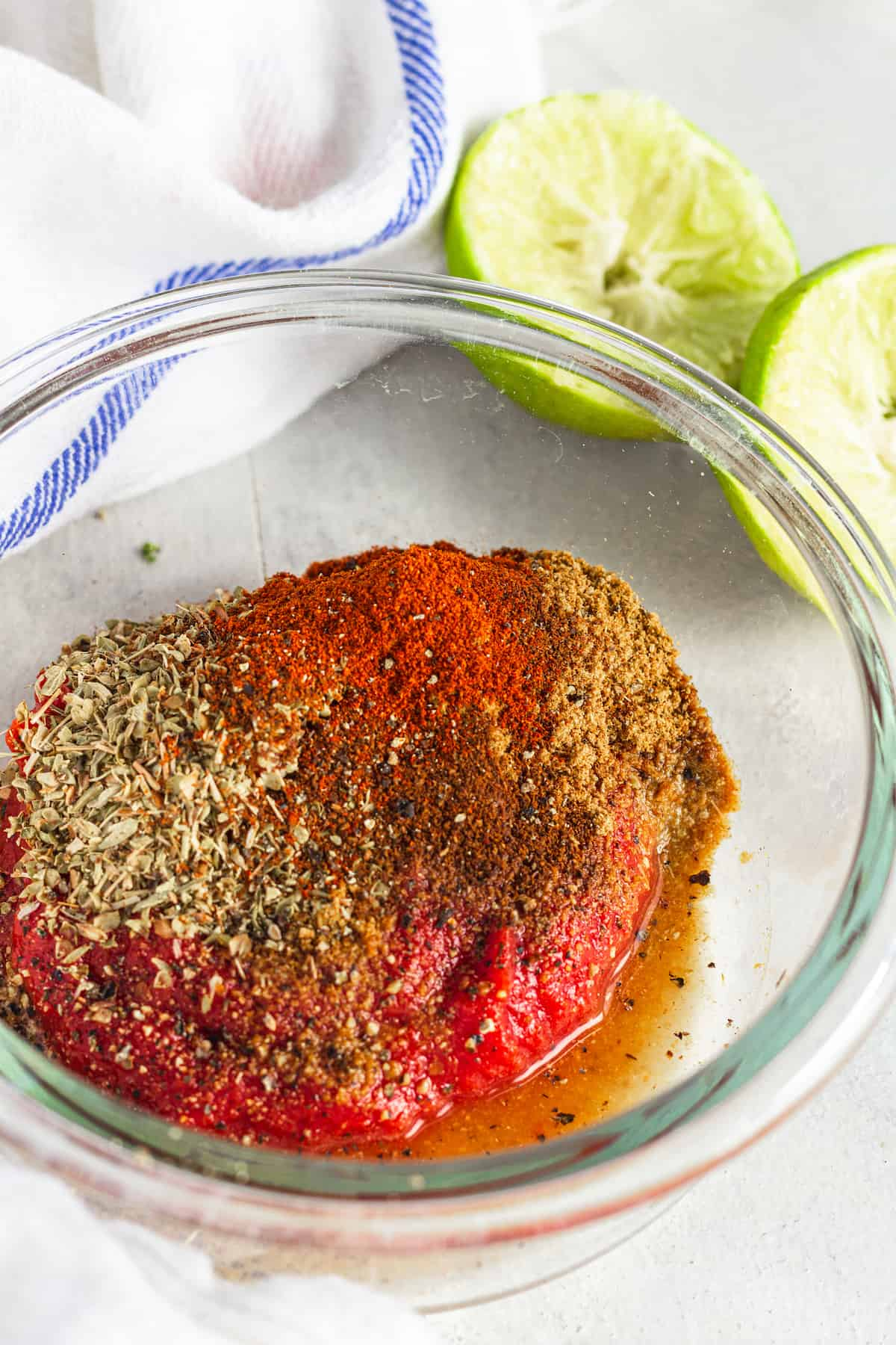 The Tomato Paste, Seasoning and Lime Juice Mixture in a Glass Bowl Beside a Juiced Lime