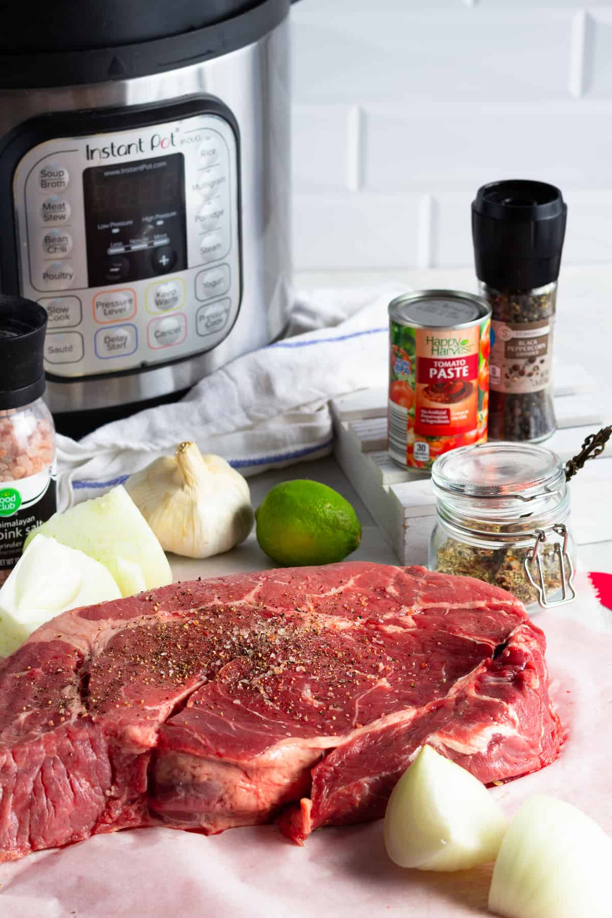 An Instant Pot, Tomato Paste, a Chuck Roast, Onions, a Lime and the Other Beef Barbacoa Ingredients