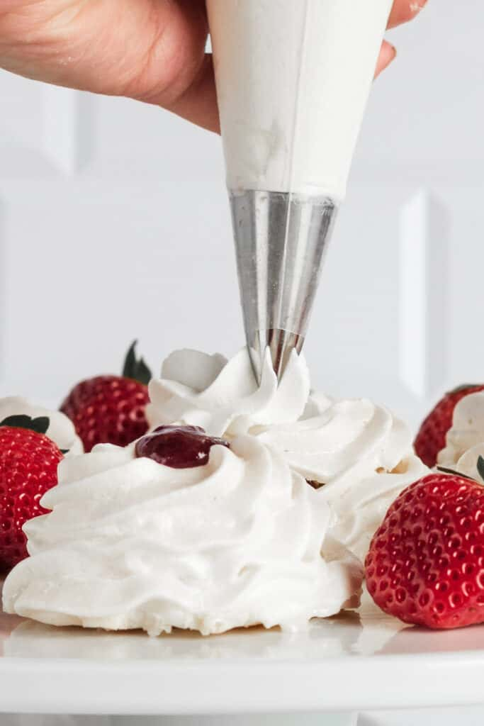 A hand piping whipped cream