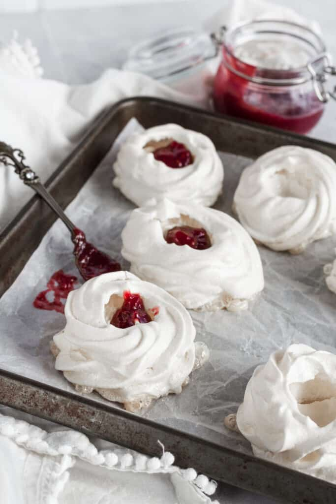 Pavlova nests being filled with strawberry filling