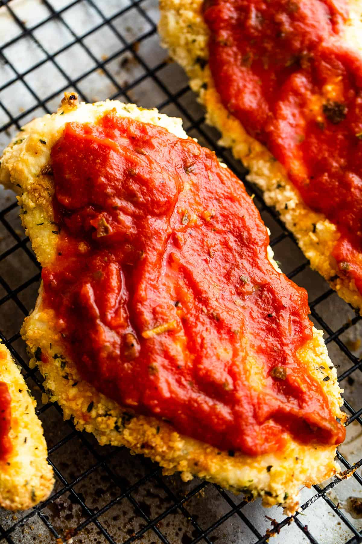 Two Pieces of Partially Cooked, Breaded Chicken with Marinara Sauce Spread on Top