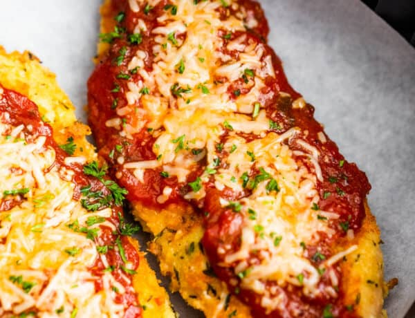 Two Pieces of Breaded, Partially Cooked Chicken Being Topped with Marinara and Shredded Parmesan Cheese
