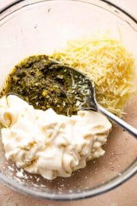 mixing together basil pesto, mayonnaise, and parmesan cheese