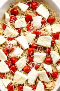 chicken caprese casserole in a white baking dish topped with fresh mozzarella chunks and cherry tomatoes