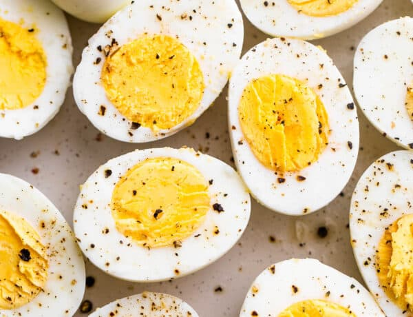 halved hard boiled eggs topped with cracked black pepper