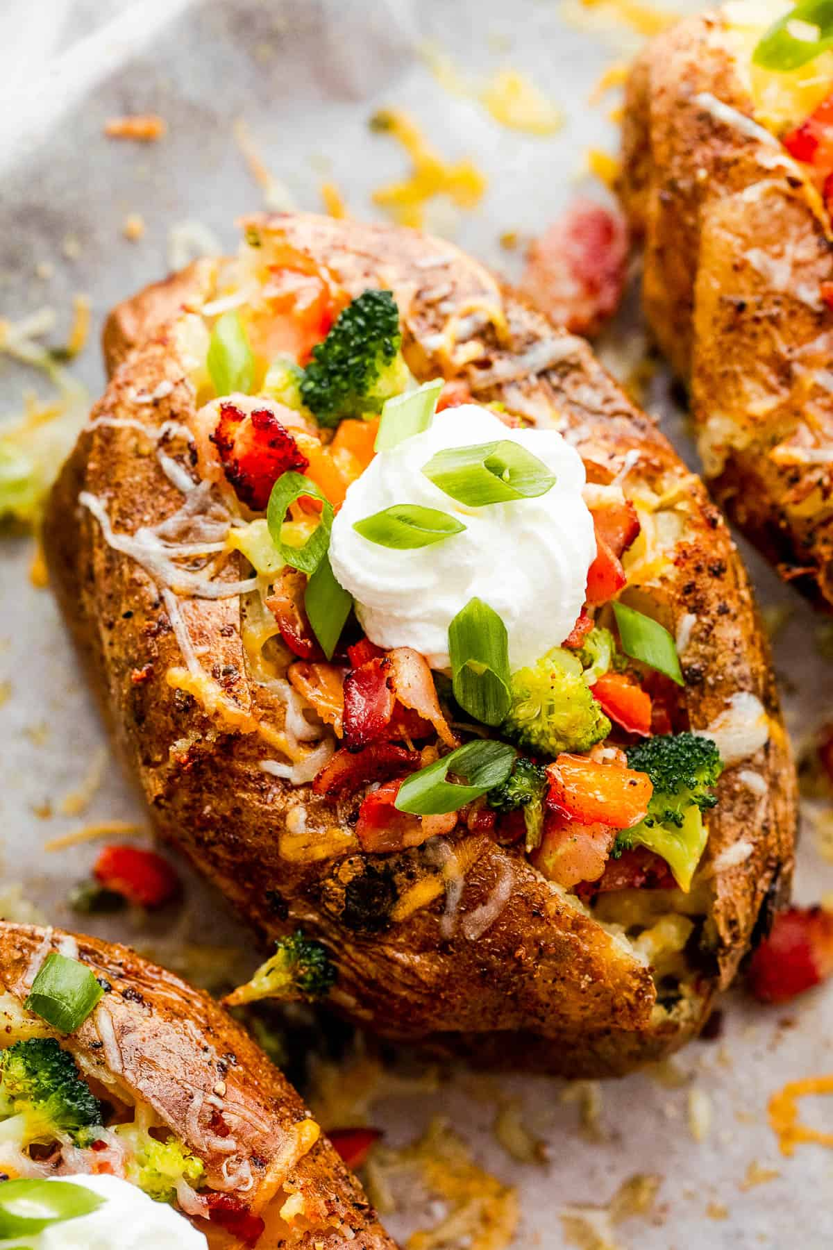 Three Instant Pot Baked Potatoes Beside Bowls of Cheese, Broccoli, Bacon, Chopped Green Onions and Sour Cream