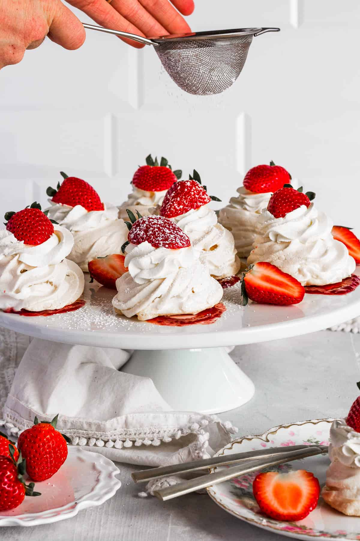Sifting confectioners sugar onto pavlovas