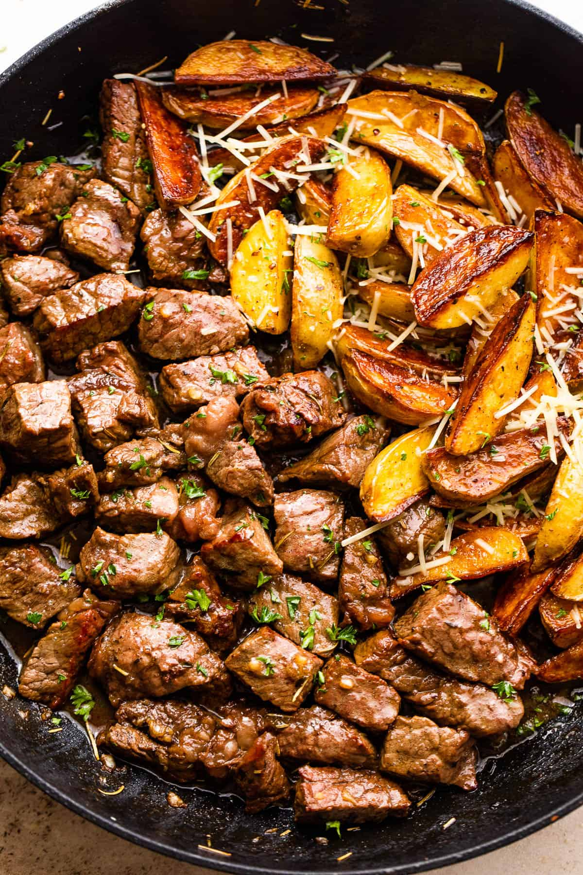 overhead shot of sirloin steak bites and quartered gold potatoes in a skillet