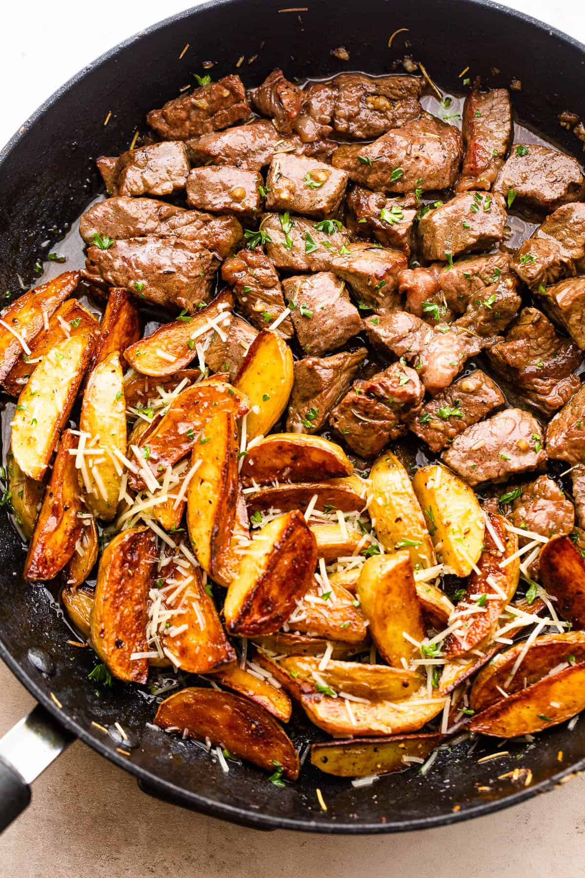 cubed steak and quartered potatoes cooking in a skillet