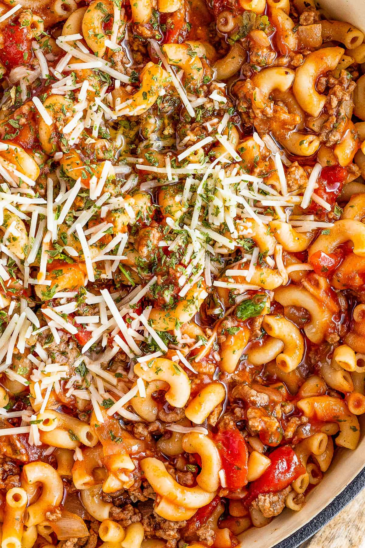 close up shot of a Gray Pot Full of American Goulash Topped with Chopped Parsley and Grated Parmesan
