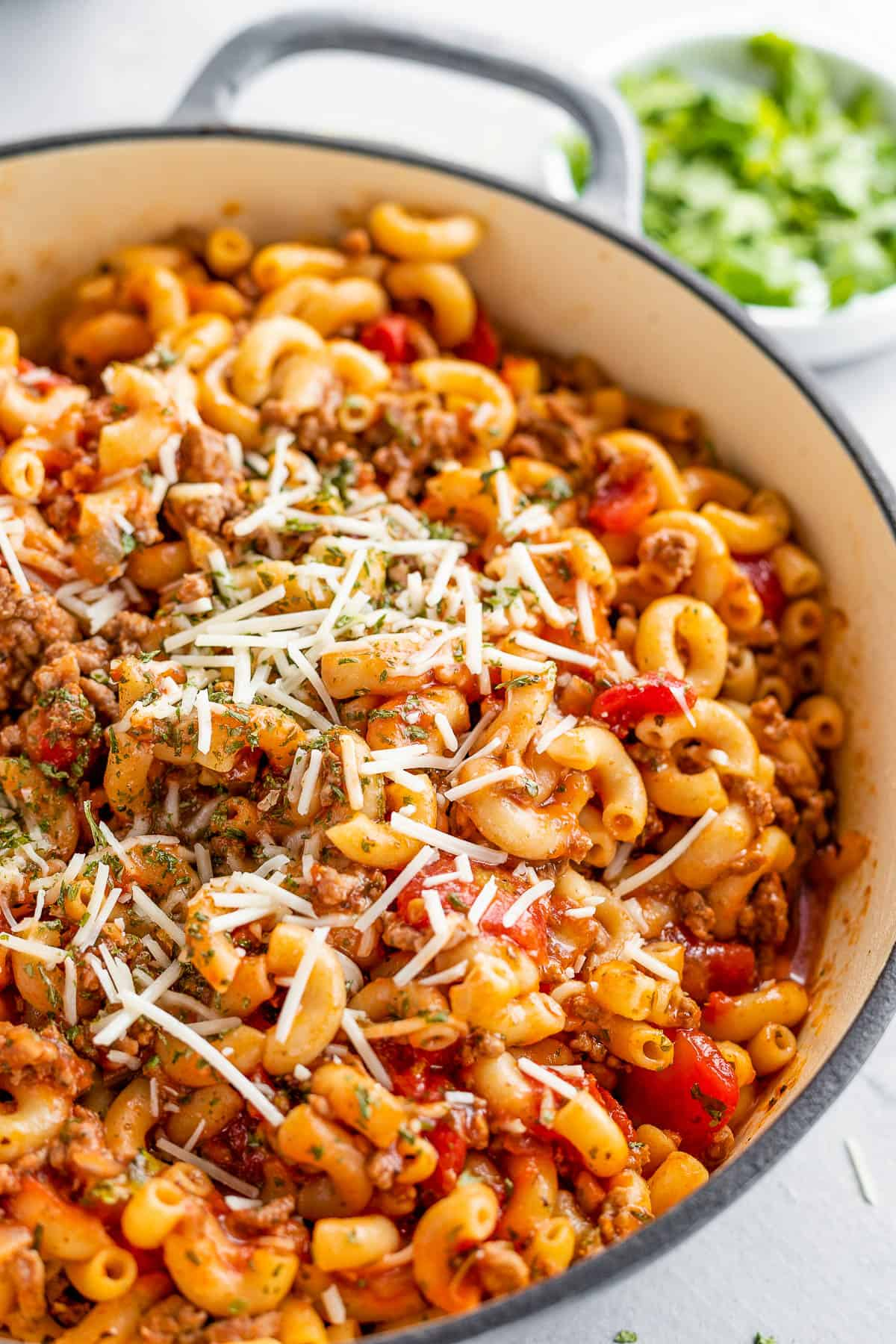 A Gray Pot Full of American Goulash Topped with Chopped Parsley and Grated Parmesan