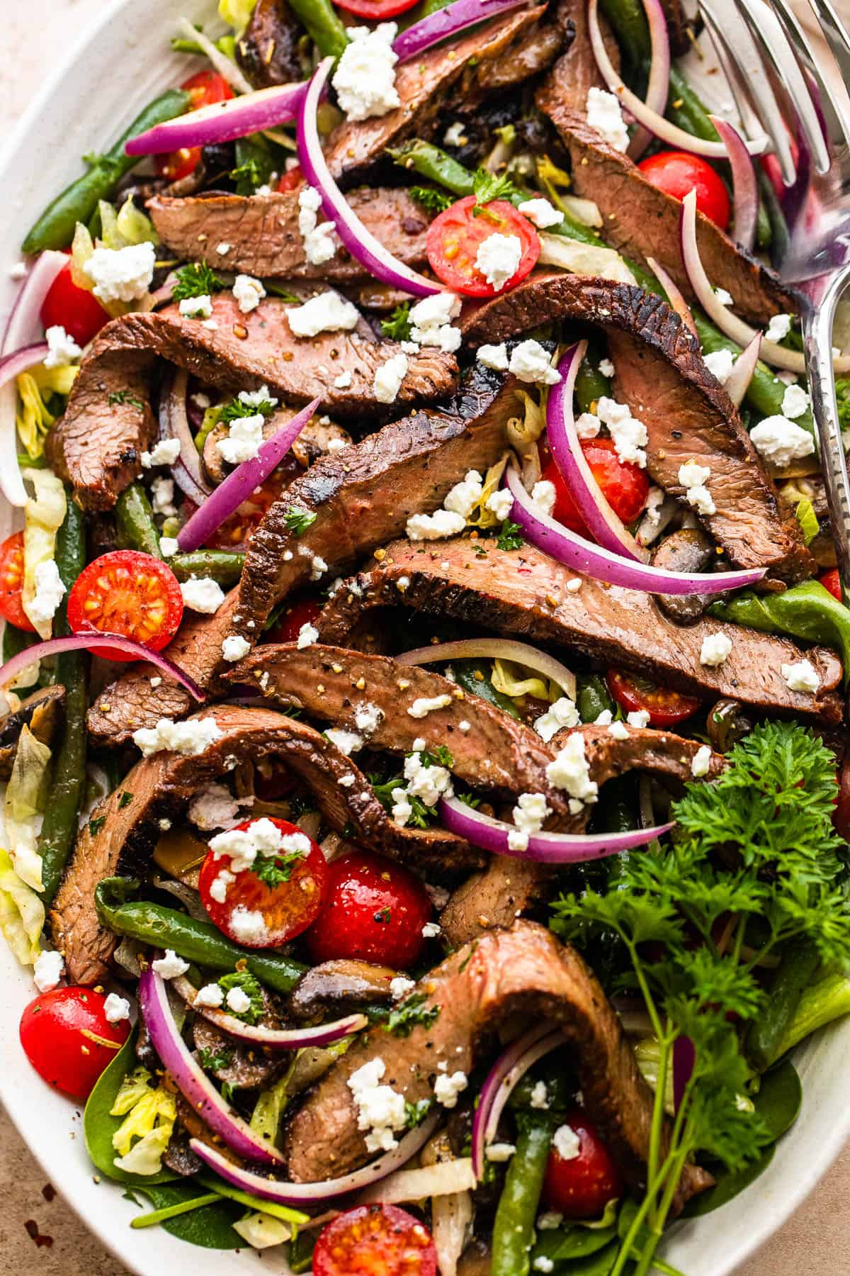 Steak Salad on a long plate topped with cheese crumbles, tomatoes, and mushrooms