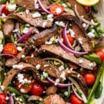 Steak Salad served on a long plate topped with cheese crumbles, tomatoes, and mushrooms