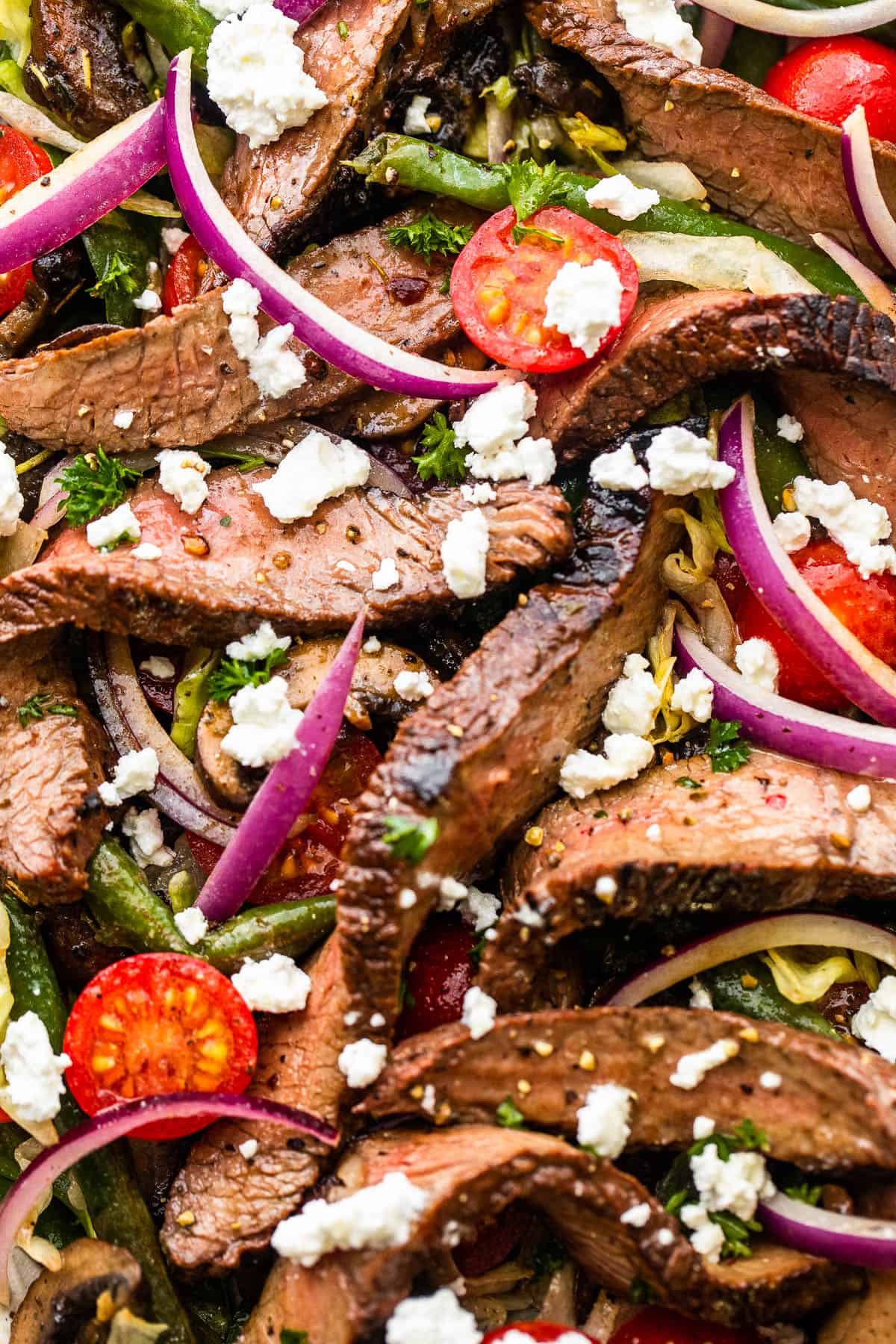 up close photo of Steak Salad on a long plate topped with cheese crumbles, tomatoes, and mushrooms