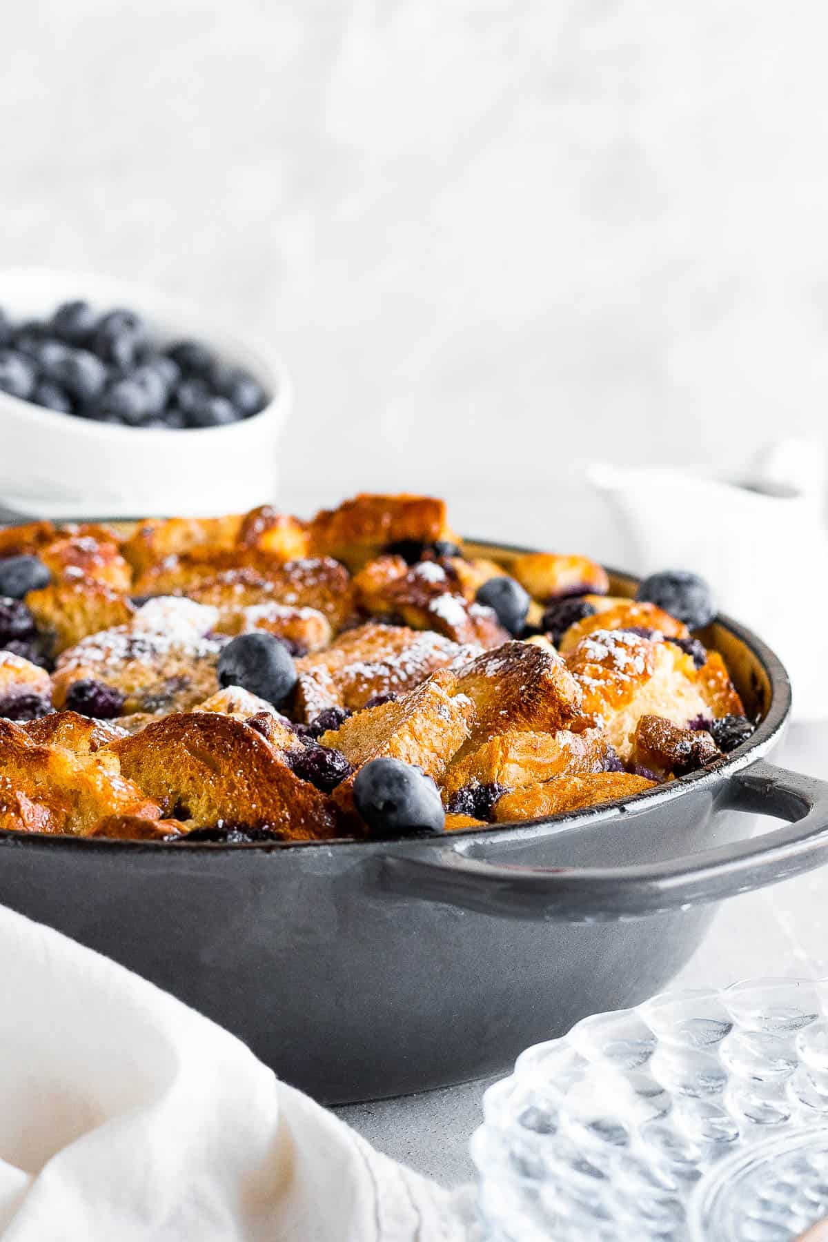 A Baked Blueberry French Toast Casserole in a Round Pan Topped with Powdered Sugar