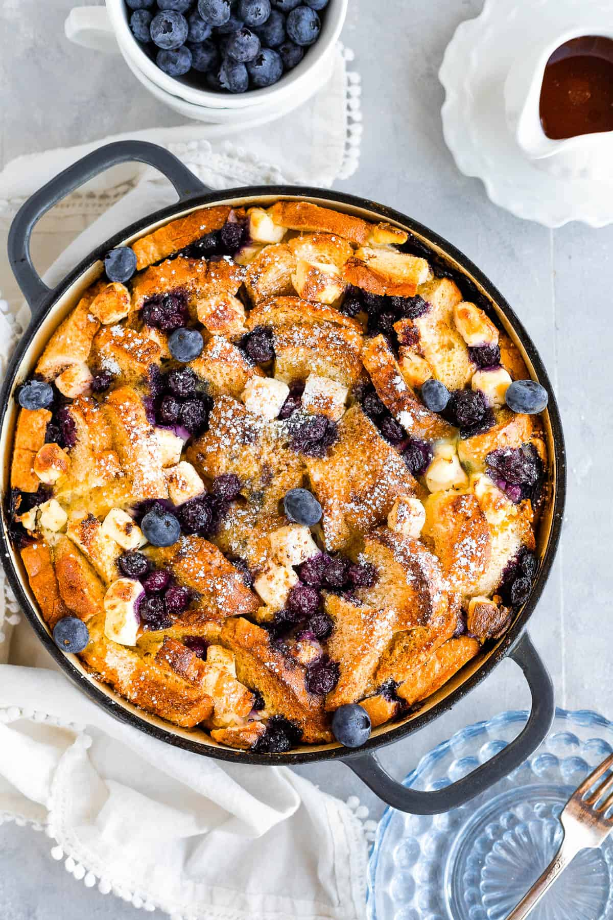 A Bird's-Eye View of a Blueberry French Toast Casserole Beside a Cup of Fresh Blueberries and a Spouted Measuring Cup of Maple Syrup
