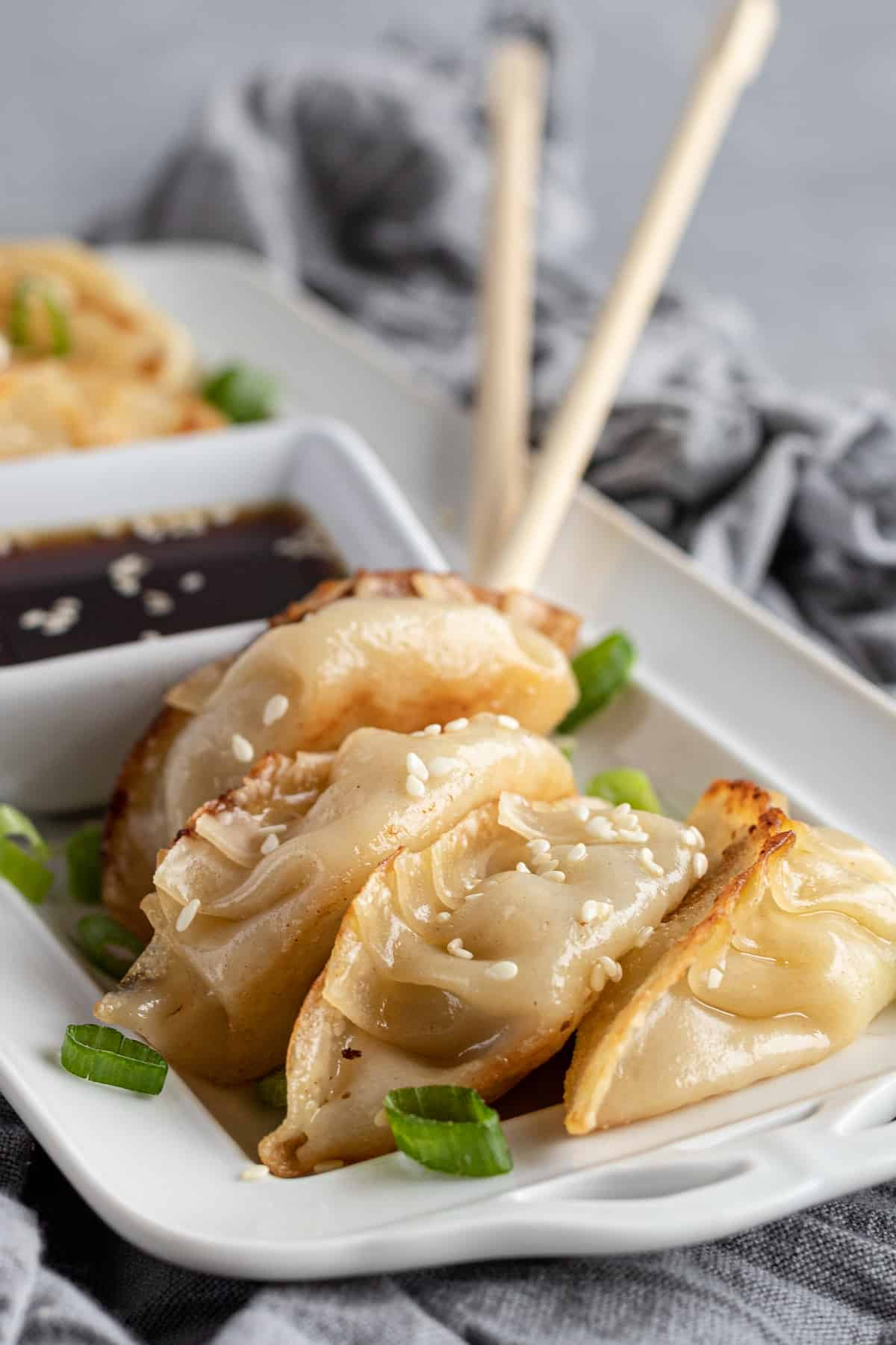Four Chicken Potstickers on a Serving Platter with Two Chopsticks in the Background