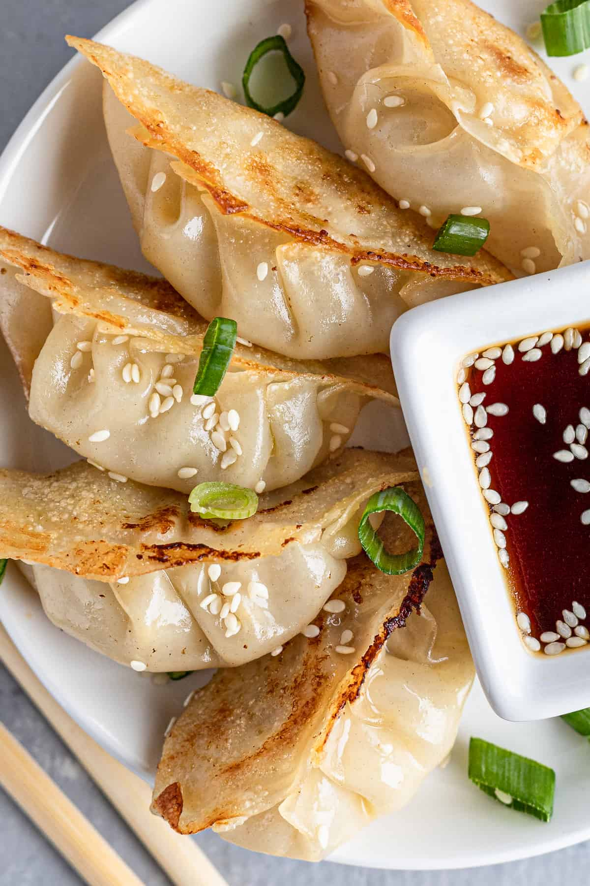 A Close-Up Shot of Chicken Potstickers on a Plate with Diced Scallions