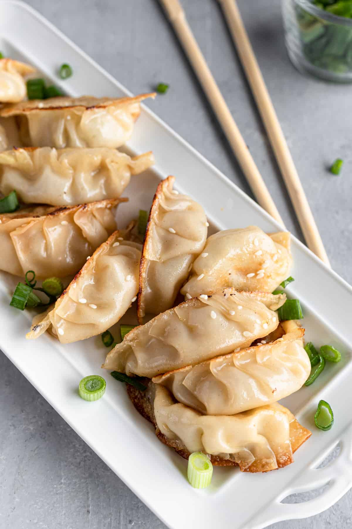 Ten Chicken Potstickers on a White Serving Platter Beside a Pair of Chopsticks