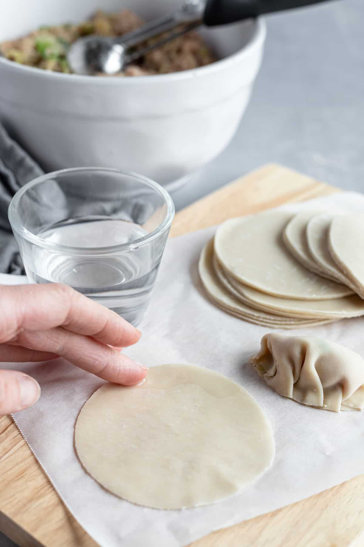 Water Being Rubbed on a Round Asian Dumpling Wrapper