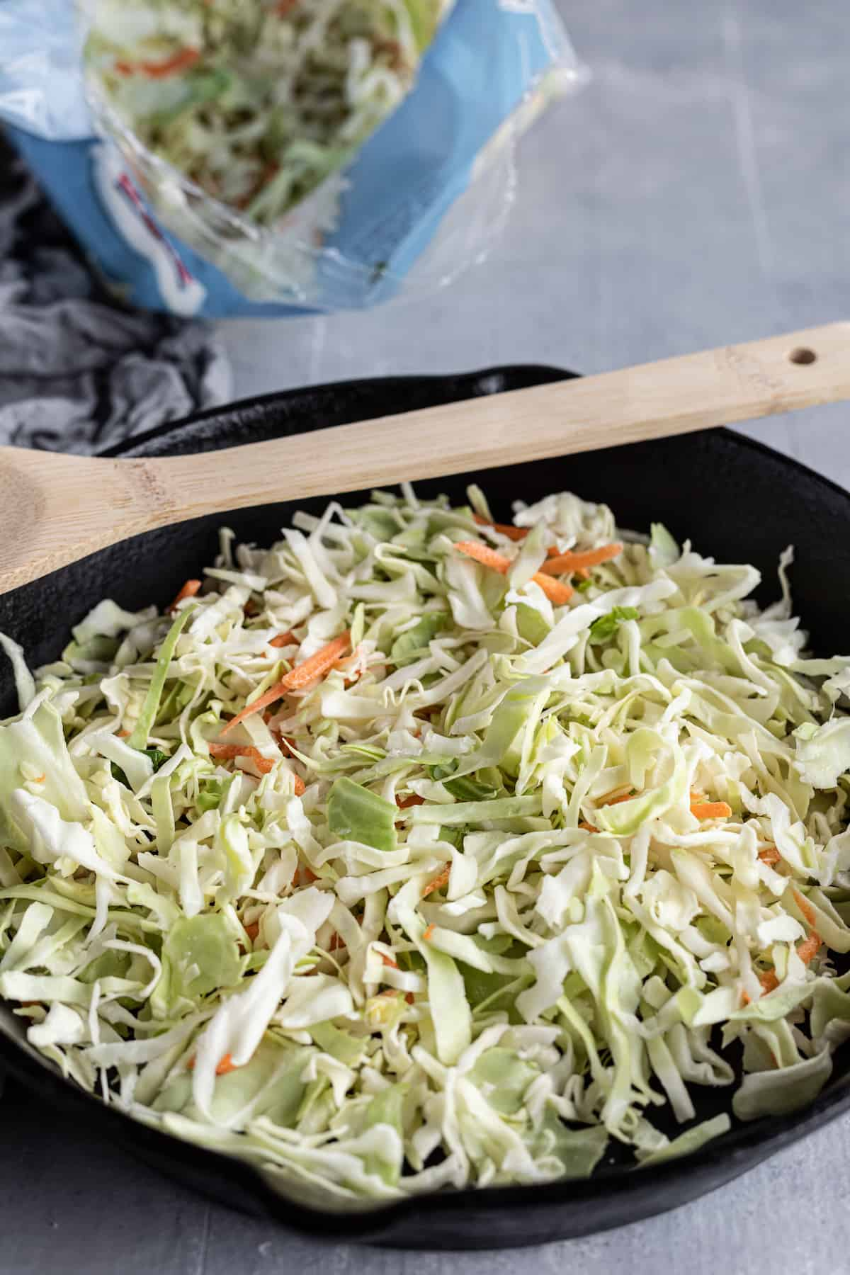 Cabbage Coleslaw in a Pan with a Wooden Spoon