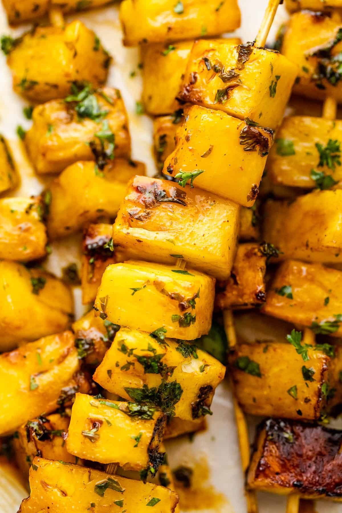 close up shot of grilled pineapple skewers served on a plate