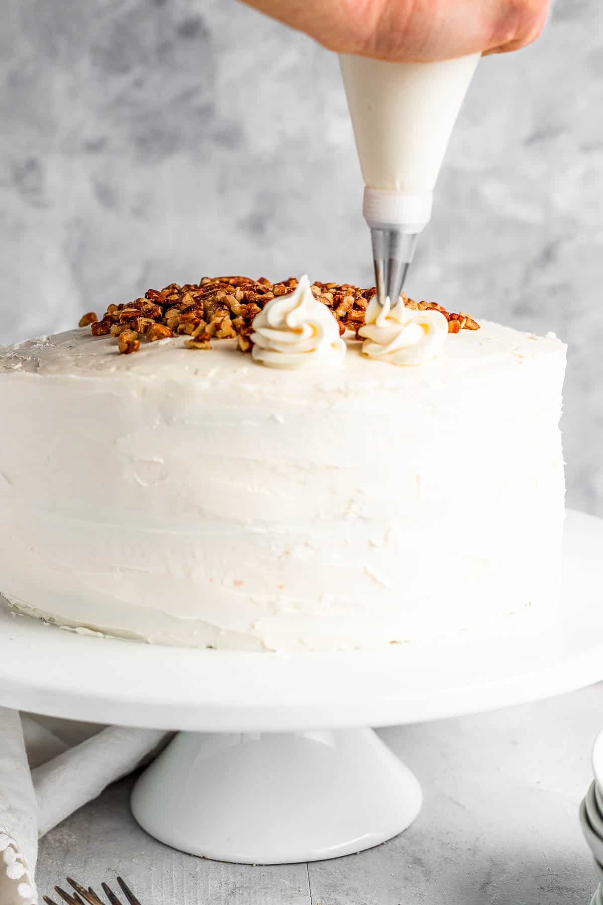 A Piping Tip Adding Swirls of Cream Cheese Icing Onto the Frosted Cake