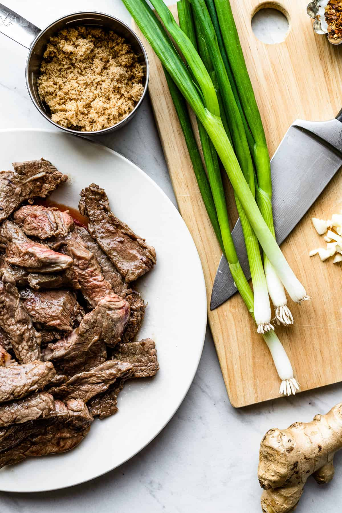 Green Onions, Garlic, Soy Sauce, Slices of Flank Steak and the Rest of the Ingredients on Two Different Baking Sheets