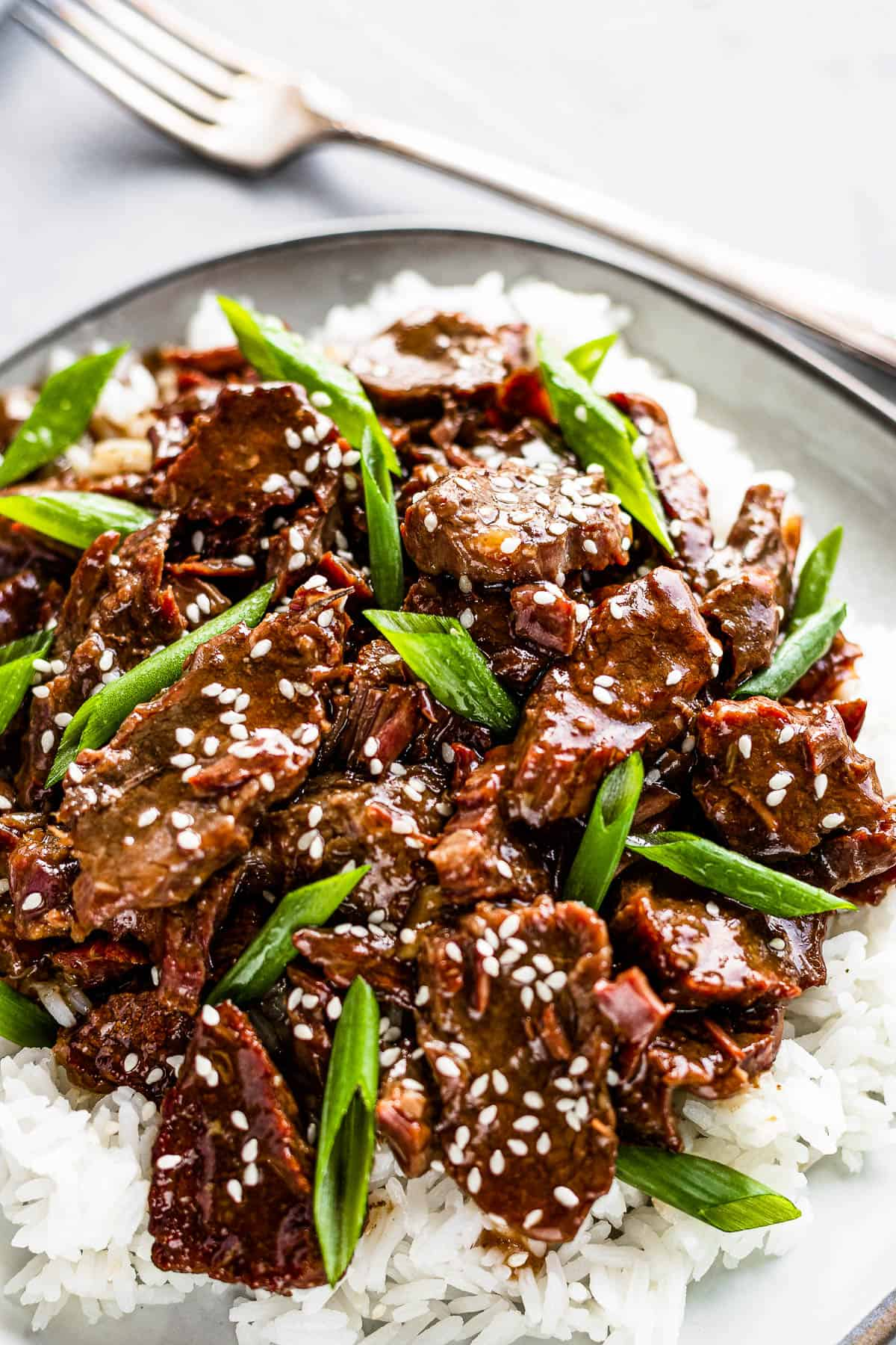 Instant Pot Mongolian Beef Over White Rice on a Gray Plate with a fork on the side