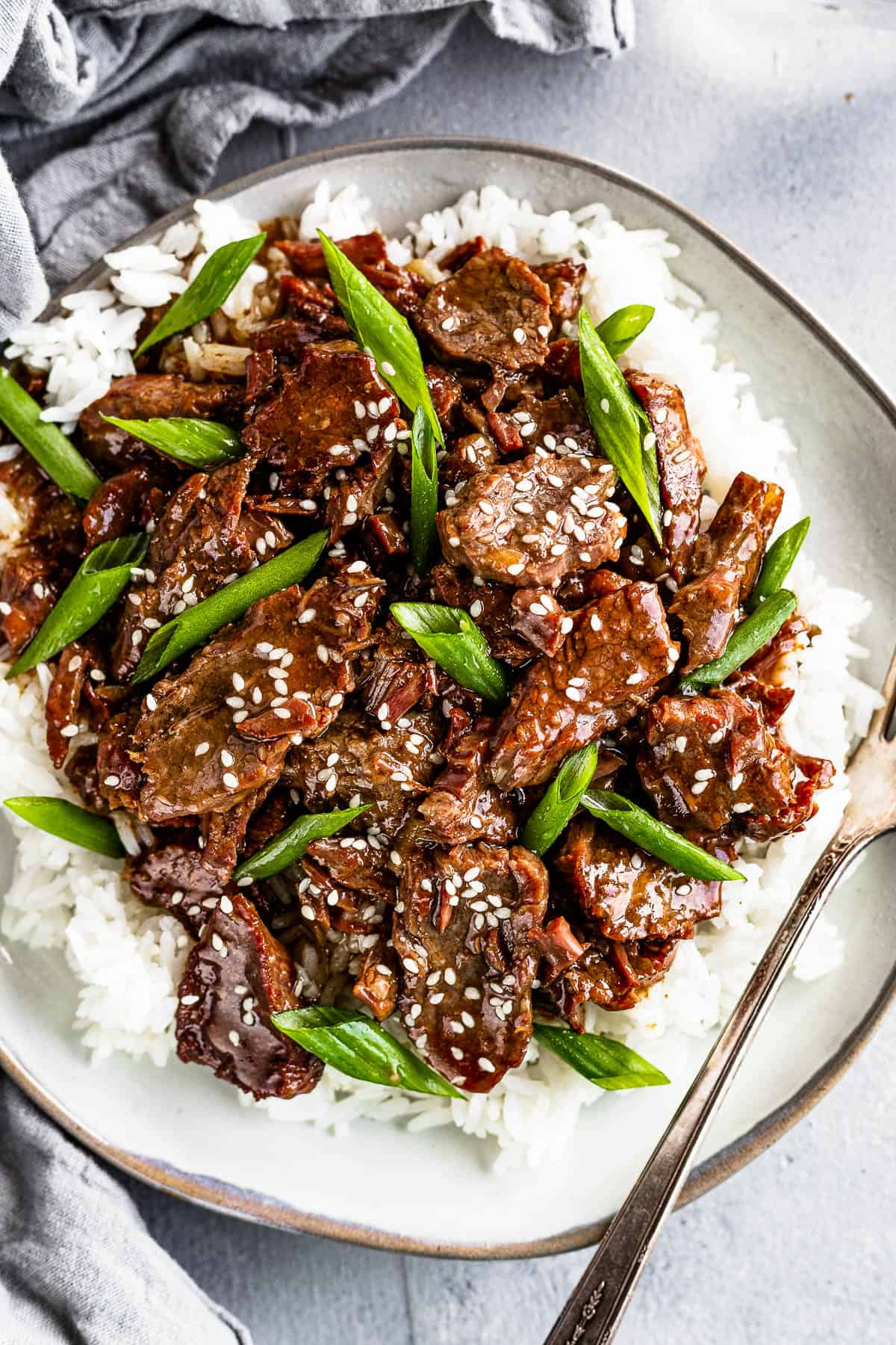 Instant Pot Mongolian Beef Over White Rice on a Gray Plate with a fork on the plate