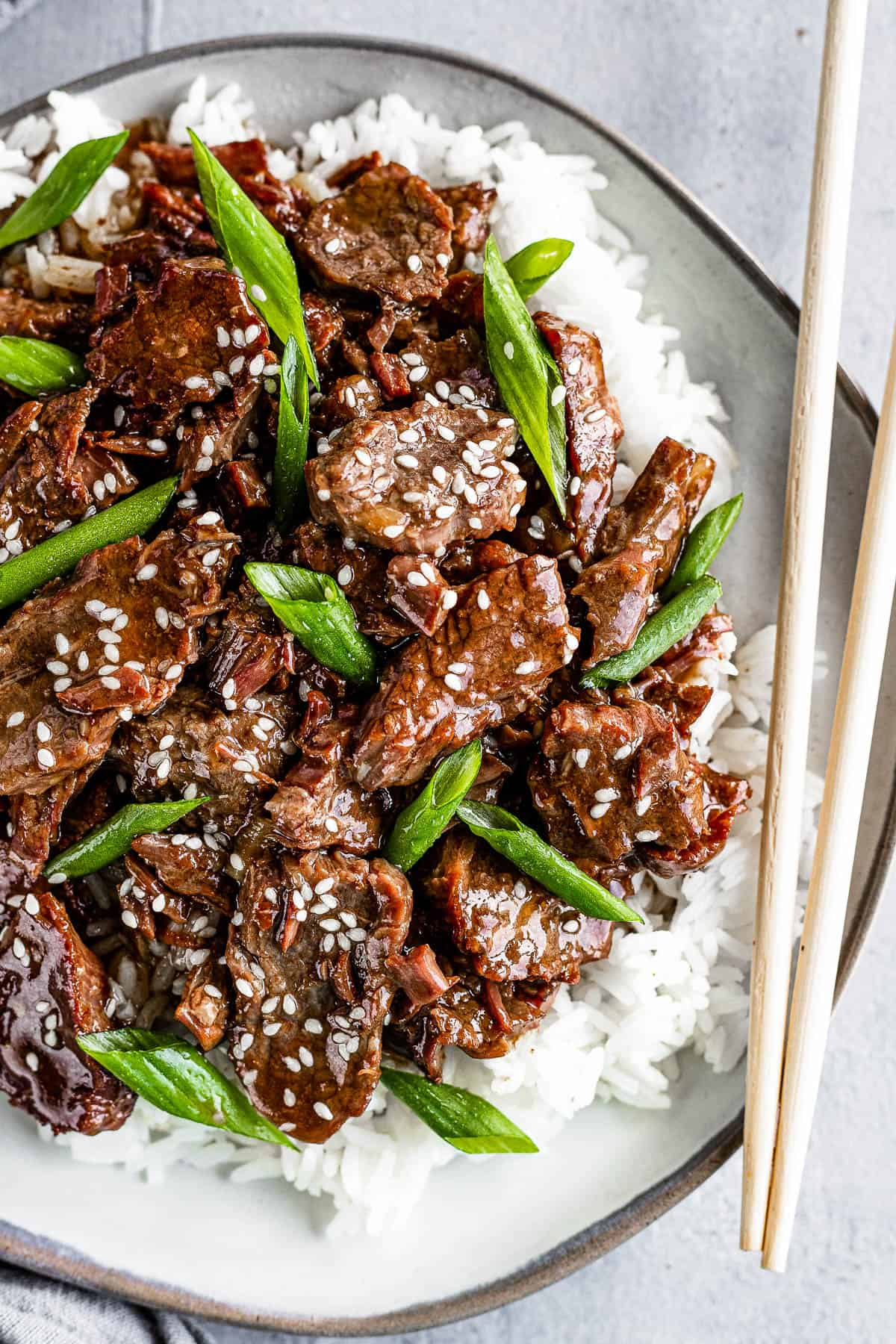 Instant Pot Mongolian Beef Over White Rice on a Gray Plate with a Pair of Wooden Chopsticks