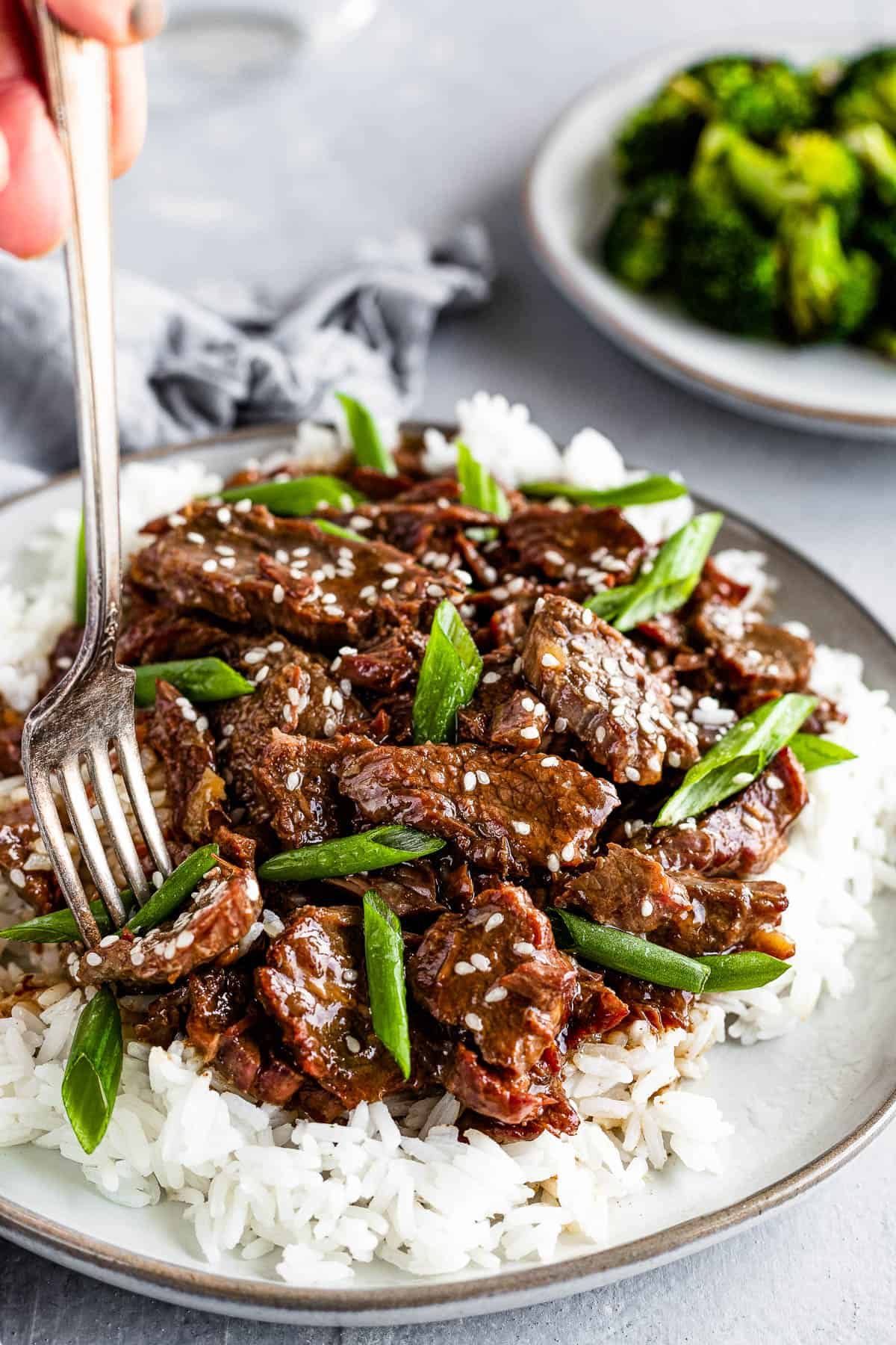 A Metal Fork Digging Into a Plate of Instant Pot Mongolian Beef Over White Rice