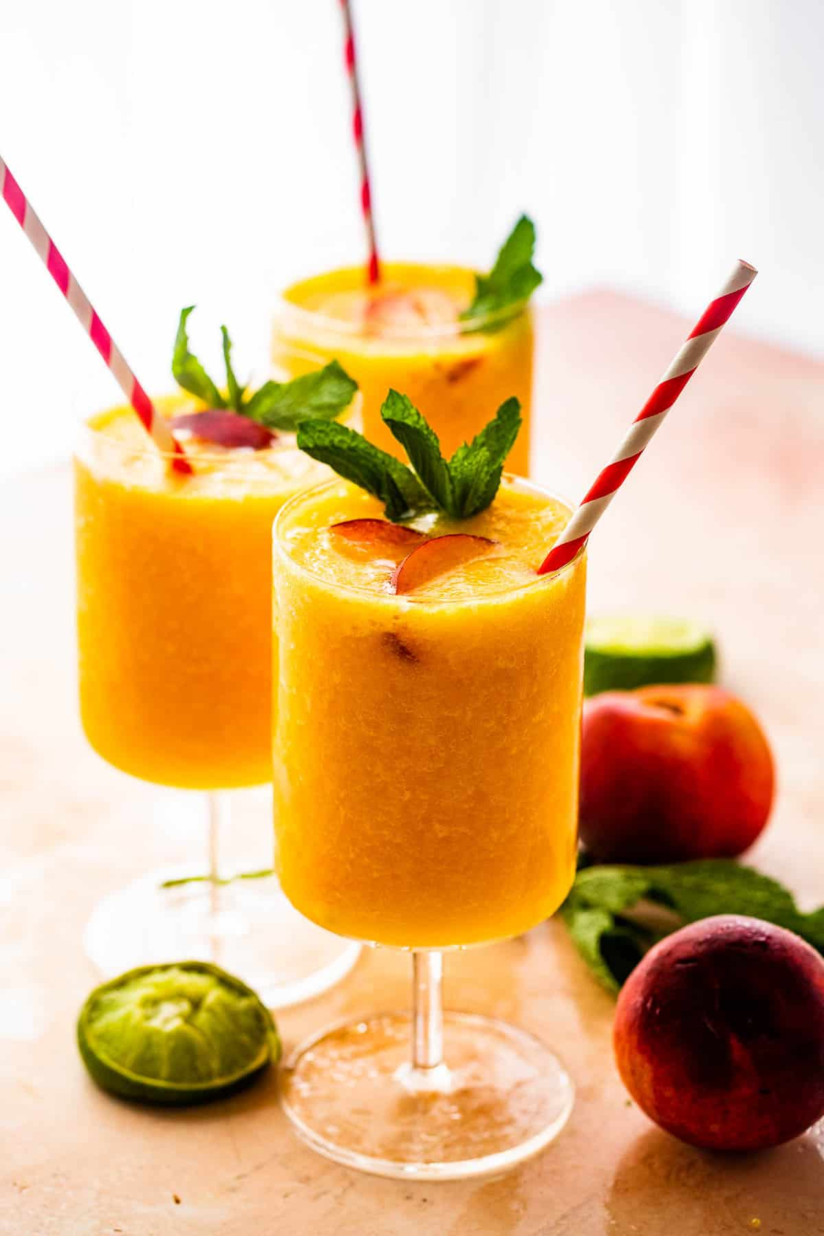 three glasses filled with peach daiquiris and garnished with mint, peach slices, and straws
