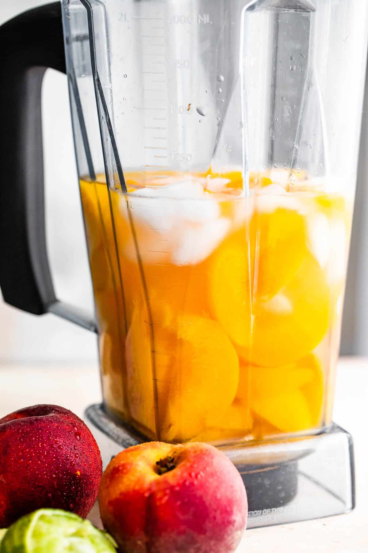 fresh peaches, rum, and ice in a blender