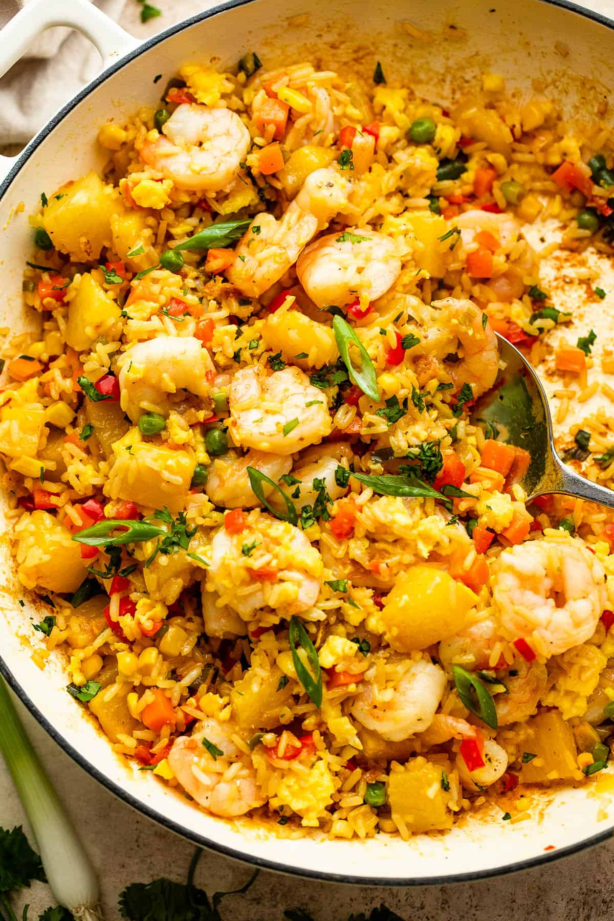 White cast iron skillet with Shrimp Fried Rice and pineapple chunks