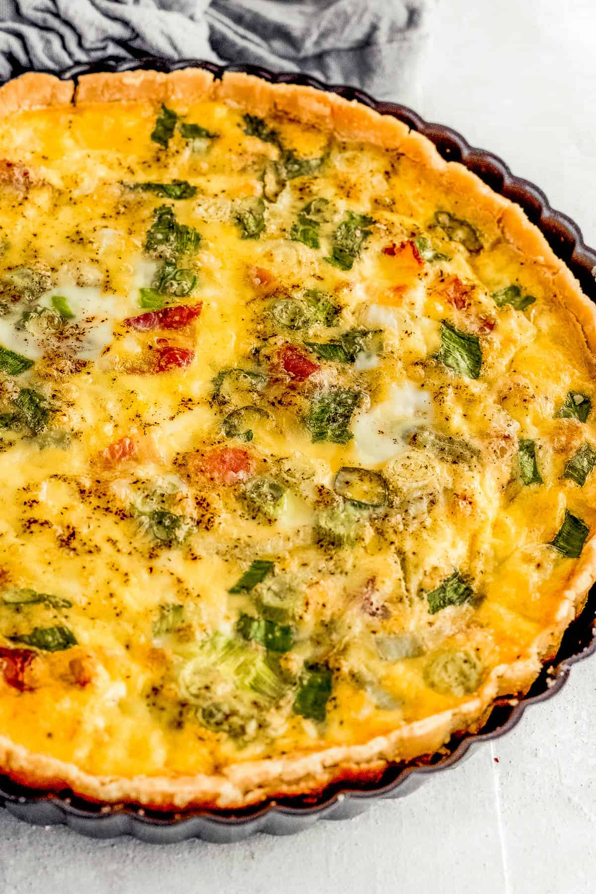 A Freshly Baked Quiche Lorraine Inside of a Black Quiche Pan