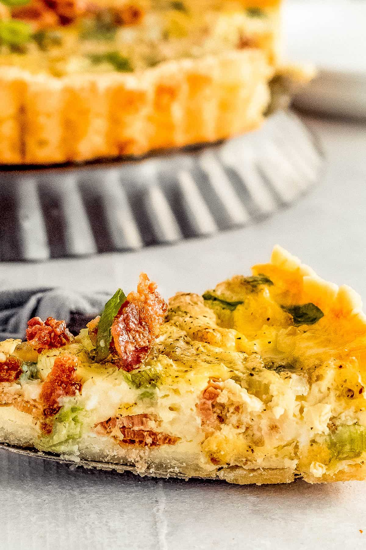 A Close-Up Shot of a Slice of Bacon Quiche Lorraine on a Metal Serving Spatula