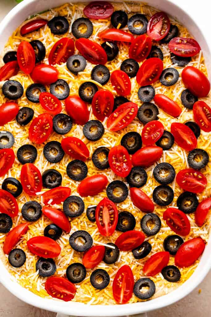overhead shot of a white baking dish with halved cherry tomatoes and sliced olives