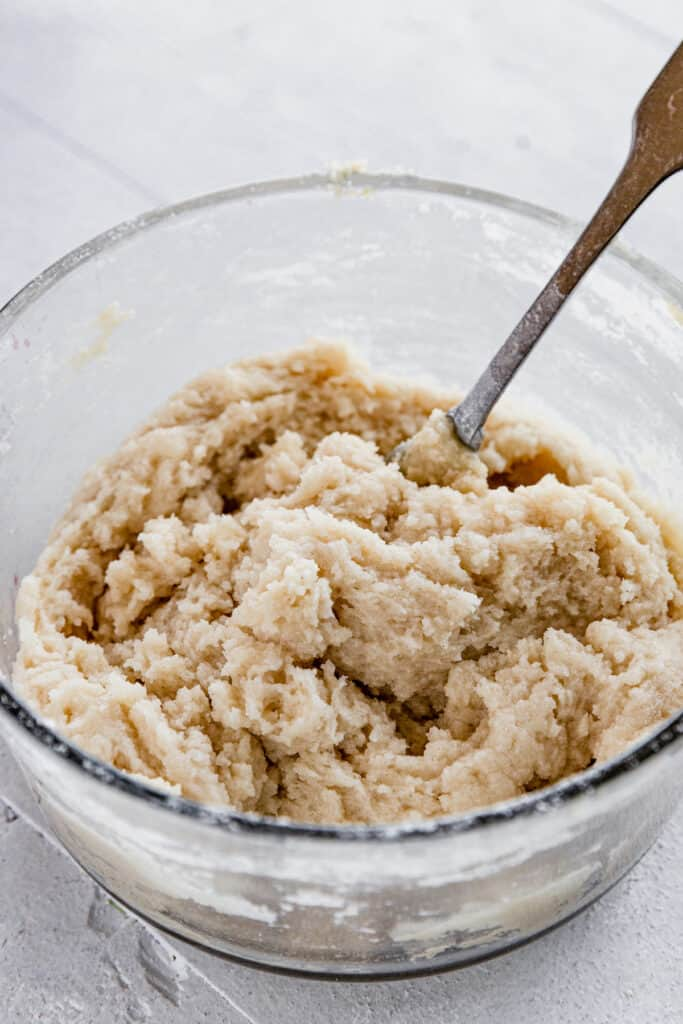 The Dough for the Topping of the Crisp in a Glass Bowl with a Metal Spoon