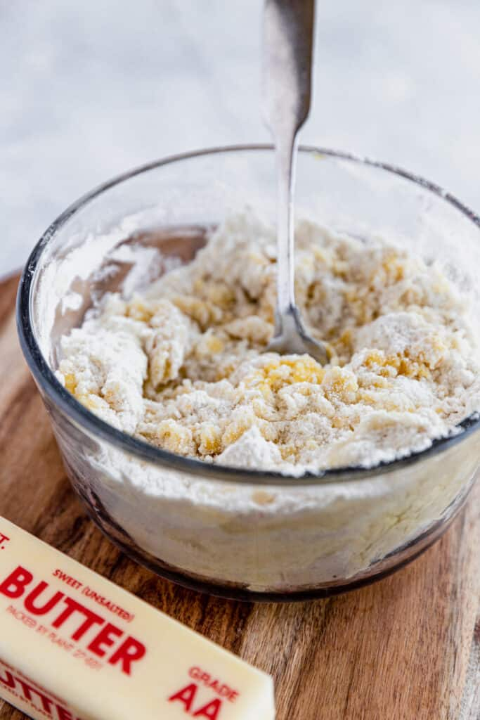 The Dough for the Cobbler Topping Being Mixed in a Glass Bowl Beside a Stick of Butter