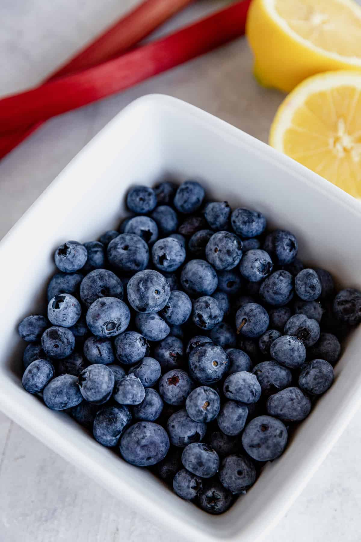 A Bowl of Blueberries Beside Rhubarb and a Fresh Lemon Cut in Half