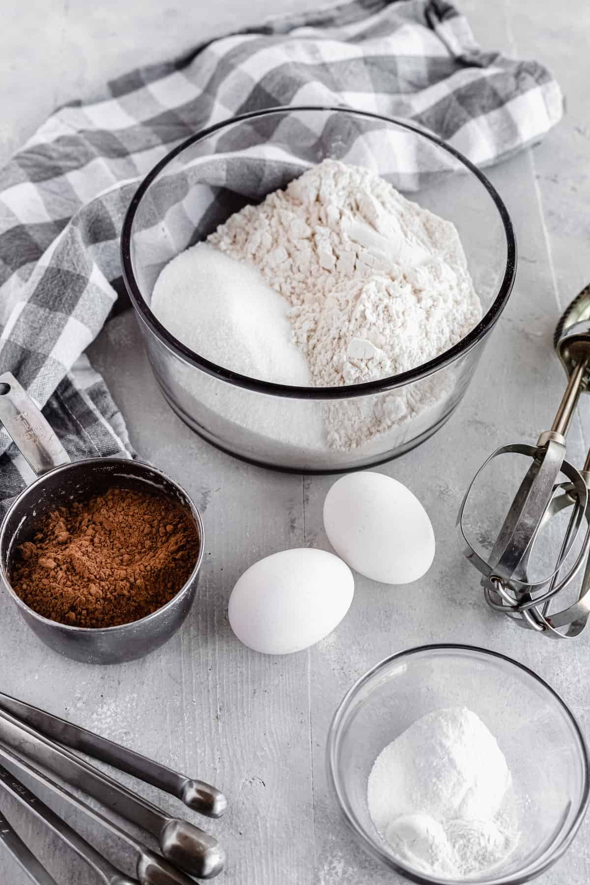 Cocoa Powder, Eggs, Baking Soda, Baking Powder and the Rest of the Cake Ingredients Arranged on a Gray Countertop