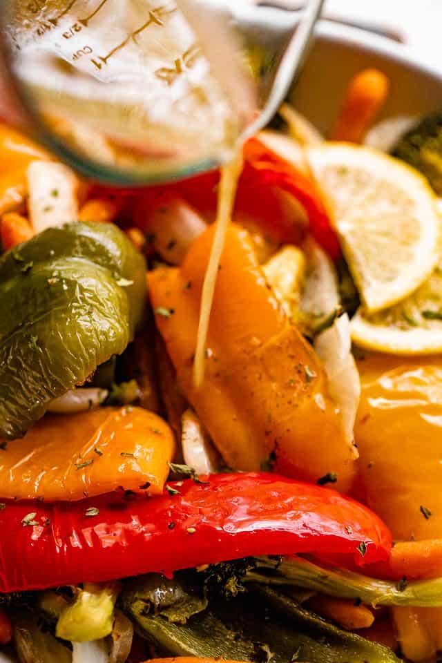 pouring lemon vinaigrette over grilled bell peppers