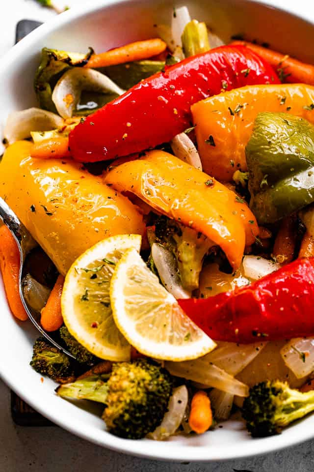 grilled vegetables served in a white bowl and garnished with lemon slices