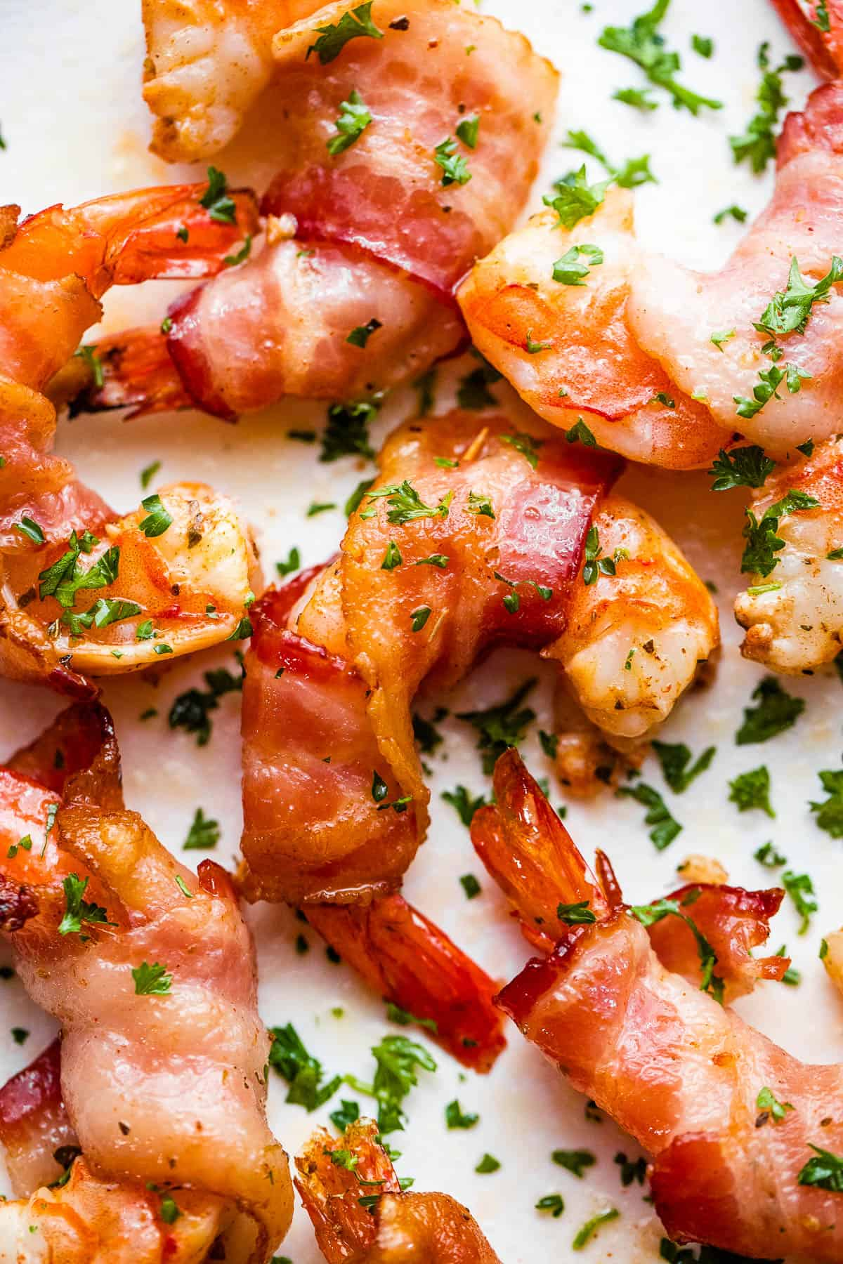 bacon wrapped shrimp arranged on a white plate and garnished with parsley