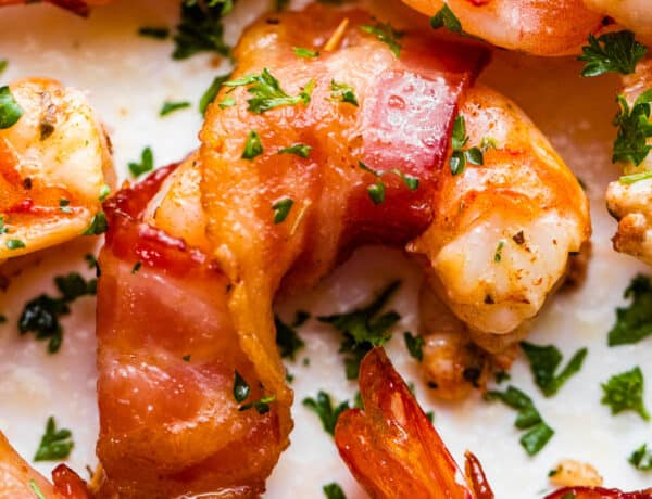 up close photo of bacon wrapped shrimp arranged on a white plate and garnished with parsley